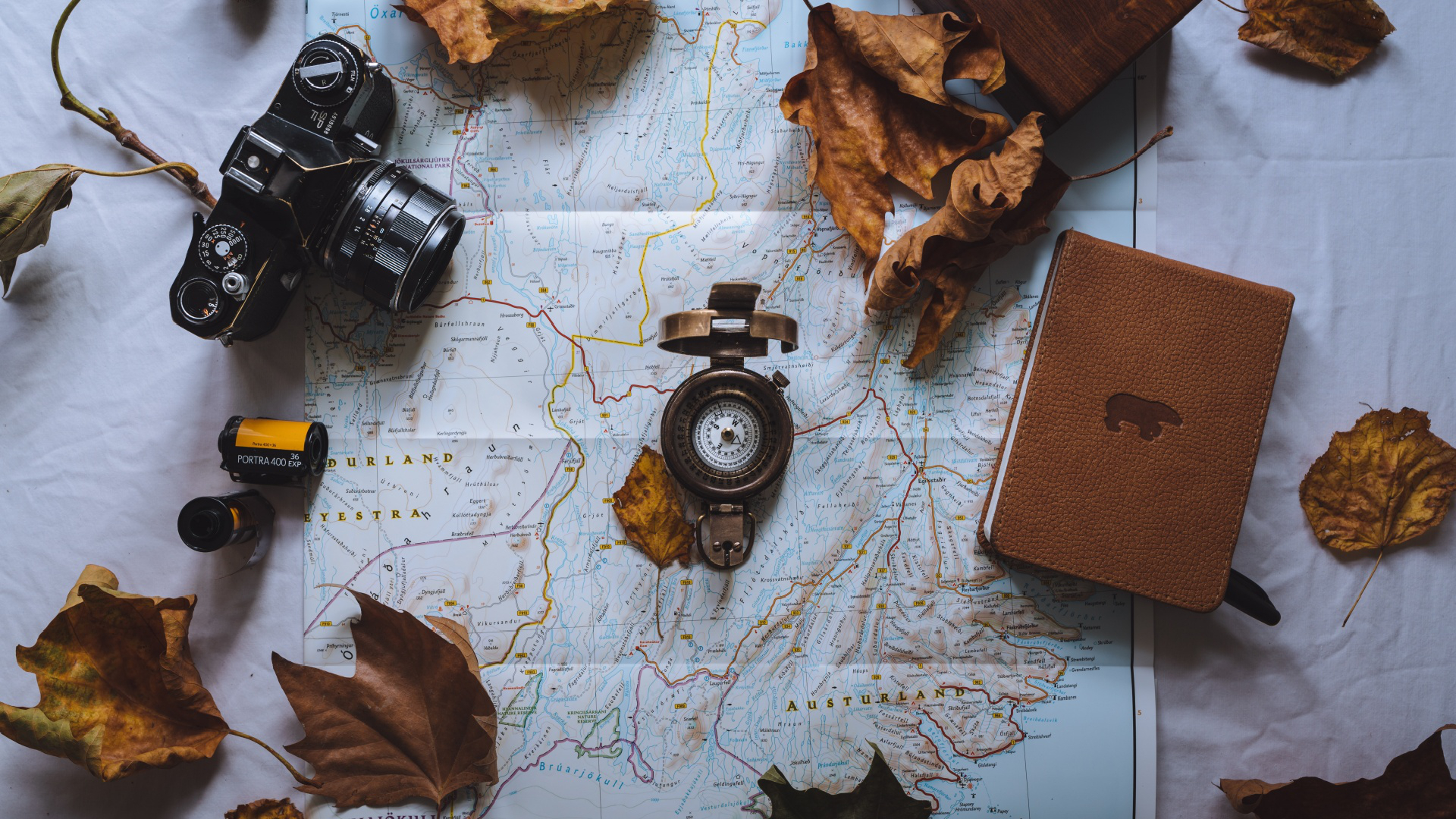jaunt,city,metropolis,background,camera,travel,move,leaves,autumn,urban center,closeup,film,change of location,fall,locomotion,compass,papermap,trip,journey