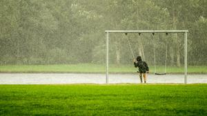 Person In Black Hoodie On Swing While Raining Free Download Image
